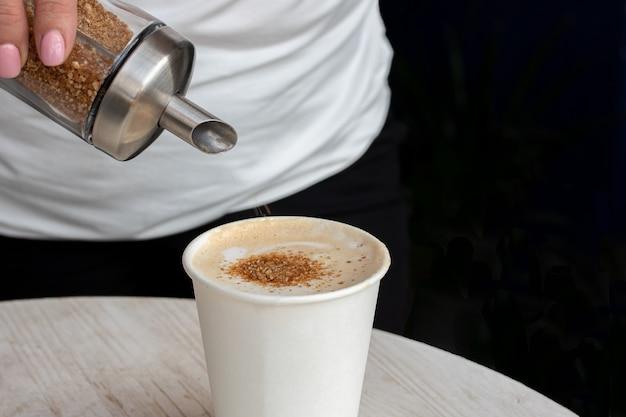 Крупный план руки, наливающей коричневый сахар в белый пластиковый стаканчик с кофе