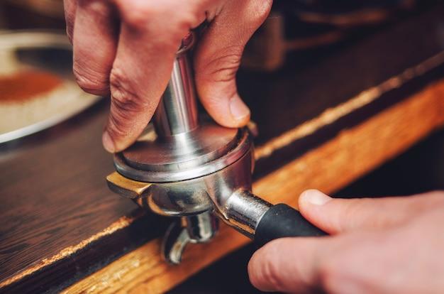 手のクローズアップは、ホルダーにコーヒーバリスタを注ぎます。ソフトフォーカス