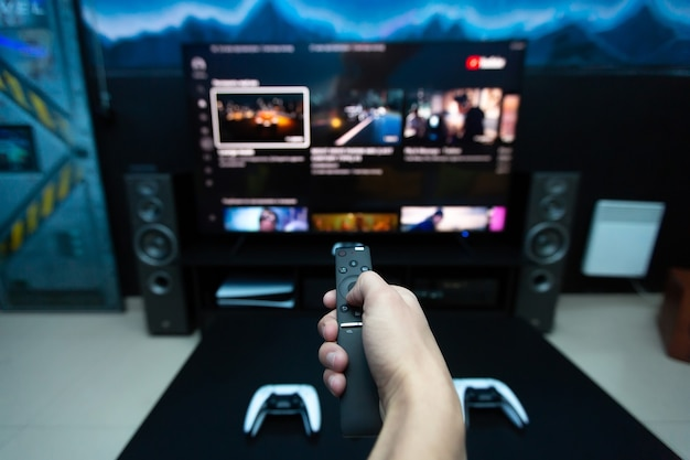 大きなテレビでコンピューター ゲームを選択している、コンソールからのリモート コントロールを持つ手のクローズ アップ。