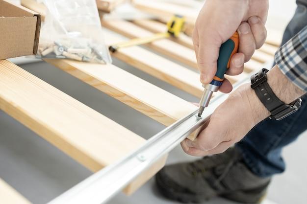 Крупным планом руки сборка каркаса кровати с помощью отвертки. концепция монтажа мебели