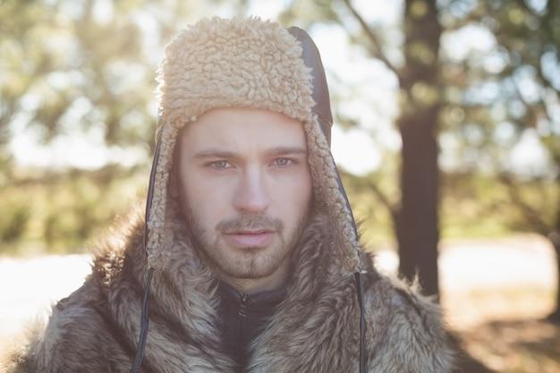 Закройте красивый мужчина в теплой одежде в лесу