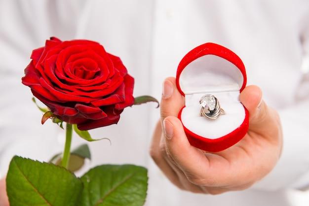 赤いバラと結婚指輪のハンサムな男のクローズアップ