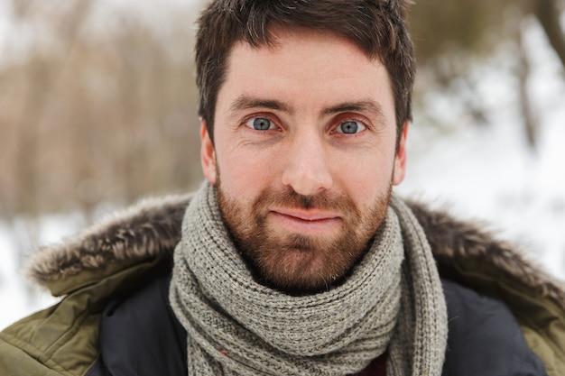 Крупным планом красивый улыбающийся молодой человек в зимней куртке гуляет на открытом воздухе