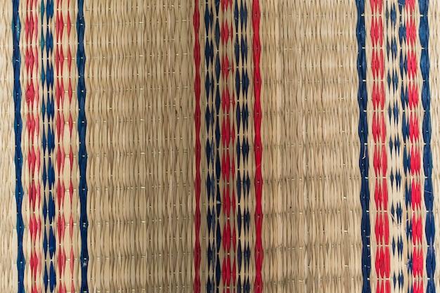 빨간색과 파란색 패턴이 삽입된 손으로 짠 매트의 클로즈업.