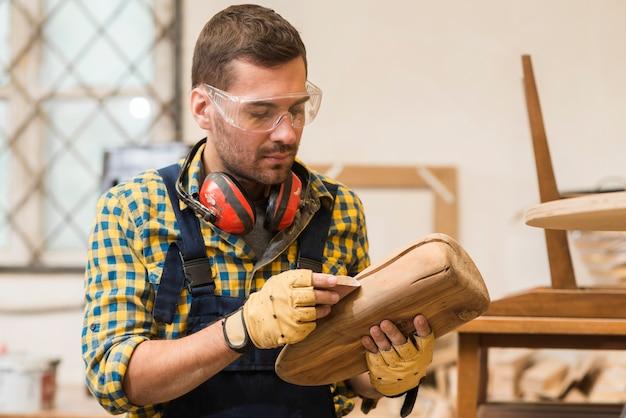 Крупным планом разнорабочий, потирая наждачной бумагой на деревянной конструкции