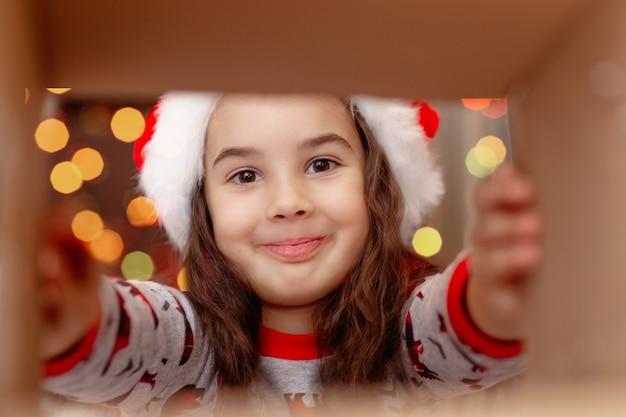 サンタクロースの帽子をかぶった幸せな女の子のクローズアップは、内部ビューで、ボックスから贈り物を取ります