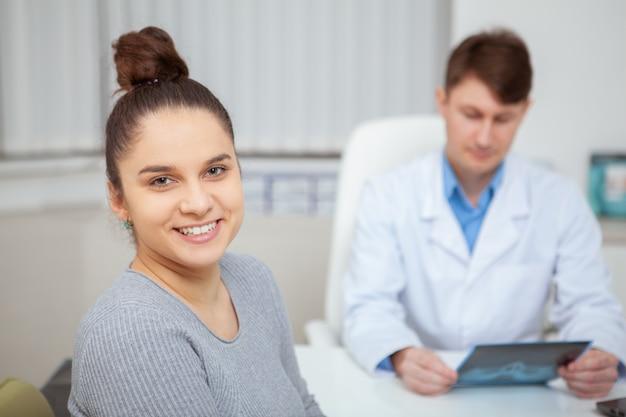 Закройте счастливой здоровой молодой женщины, улыбающейся после медицинского приема со своим врачом в больнице