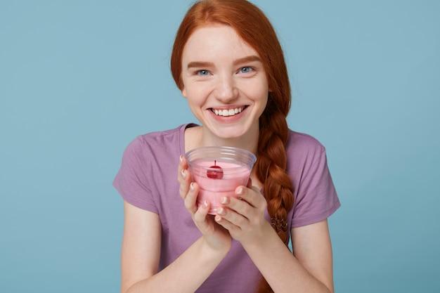 Крупным планом счастливая рыжеволосая девушка с косой улыбкой мило держит в руках стакан вишневого йогурта