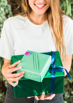 Close-up of a happy woman holding green gift boxes