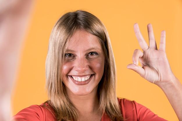 Конец-вверх счастливой женщины показывая о'кеы жест на предпосылке студии