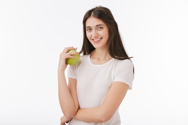 孤立した幸せな若い美しい女性のクローズアップ、青リンゴを示しています