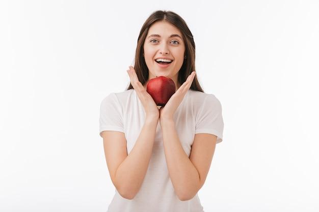 孤立した幸せな若い美しい女性のクローズアップ、赤いリンゴを示しています