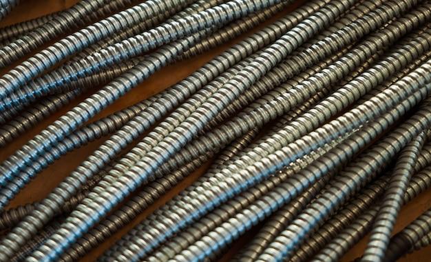 工場で相互接続されたナットを備えた金属製の柔軟なチューブの巨大な束のクローズアップ