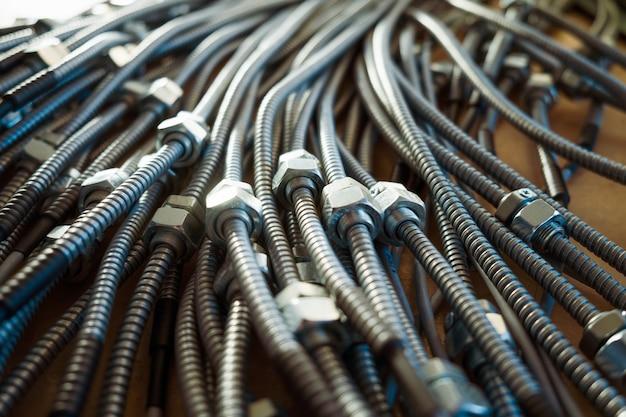 공장에서 상호 연결된 너트가있는 거대한 금속 유연한 튜브의 근접 촬영