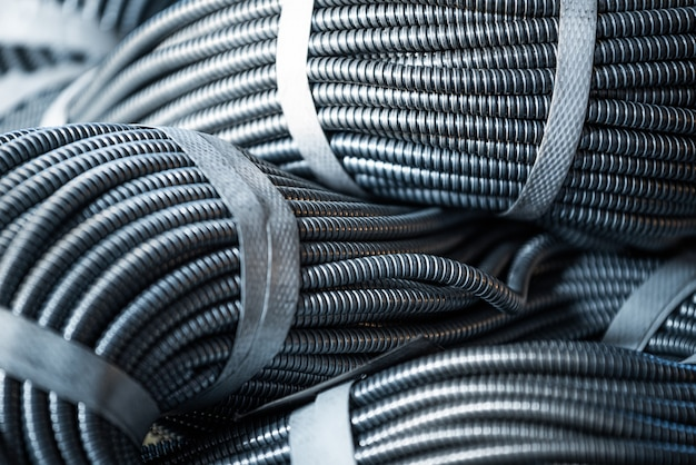 공장 또는 산업 공장에서 상호 연결된 거대한 금속 연성 튜브 묶음의 확대 그림입니다. 현대 광업의 개념 또는 첨단 산업의 it