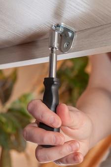 육각 트러스 막대 조정 렌치로 인간의 손을 클로즈업하여 너트를 조여 집에서 가구를 조립합니다.