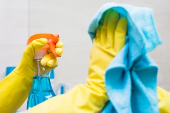 Close-up of a janitor's hand cleaning mirror with detergent and cloth