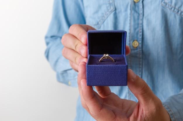 Крупный план шкатулки для драгоценностей с двумя элегантными золотыми кольцами, из которых одно с бриллиантом.