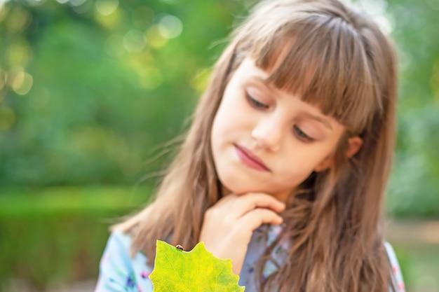 Крупный план божьей коровки на листе дерева в руке маленькой милой девочки. выборочная фокусировка изображения.