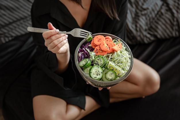 여성의 손에 갓 준비한 야채 샐러드와 함께 큰 그릇 닫습니다