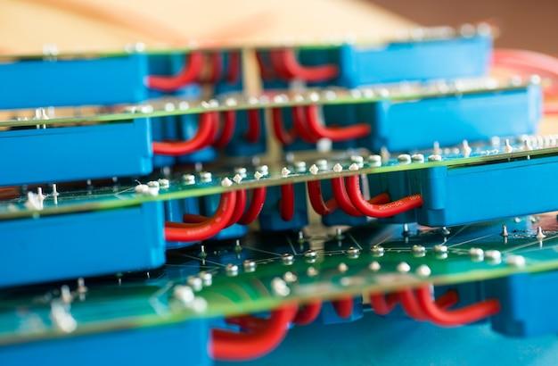 군사 장비 공장에서 빨간색 hi 전압 전선과 파란색 릴레이가 연결된 대형 녹색 미세 회로의 클로즈업. 생산에서 새로운 hi-전압 기술의 개념