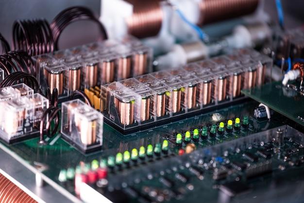 군사 장비 공장에서 전선과 플러그가 연결된 대형 녹색 미세 회로의 클로즈업. 생산의 새로운 비밀 기술의 개념