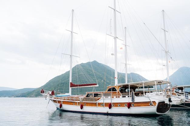ペラストの山の近くで収縮した帆を備えた大型ヨットのクローズアップ