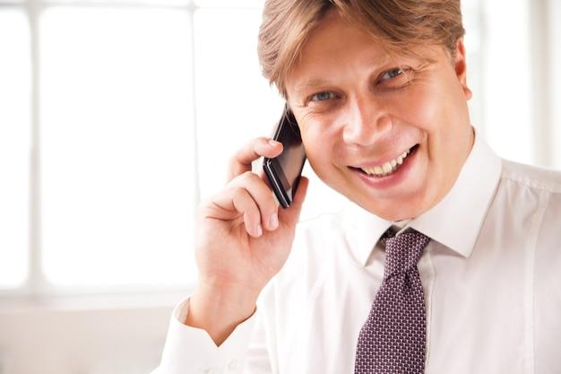 그의 사무실에서 전화로 웃는 사업가의 클로즈업