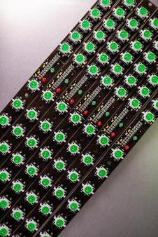 緑色のライトインジケーターのledパネルのクローズアップが制作中です。軍事的および戦略的目的のための機器の工業生産の概念