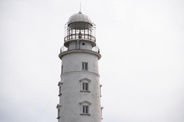 曇り空を背景にした灯台のクローズアップ。マリンテーマ。オーシャンコースト。