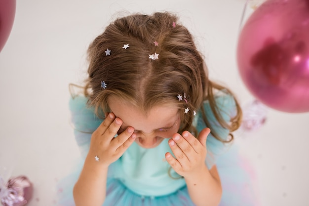 Крупный план маленькой девочки, играющей с конфетти на праздничном фоне