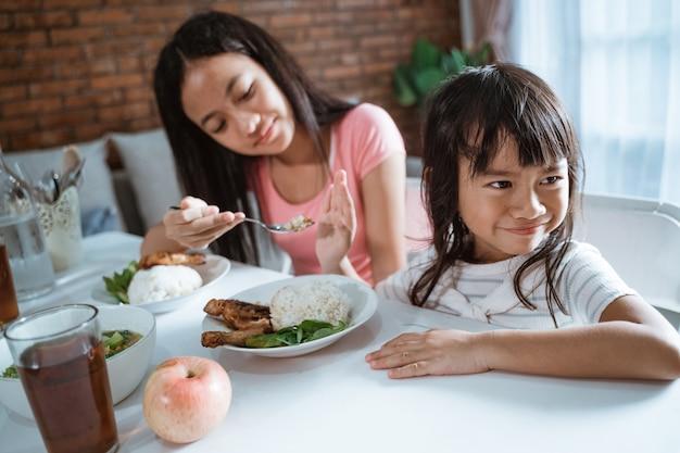彼女の姉が彼女の食べ物を与えるとき、小さな女の子のクローズアップは食べることを拒否します