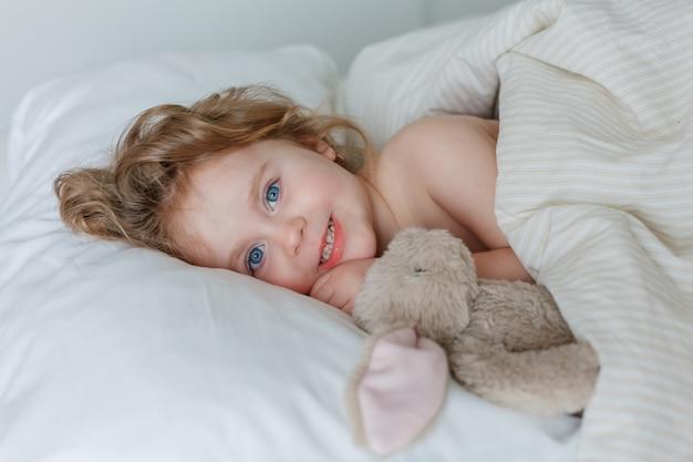 Крупный план маленькой девочки, спящей и обнимающей своего плюшевого кролика. расслабление. здоровый сон. уютный.