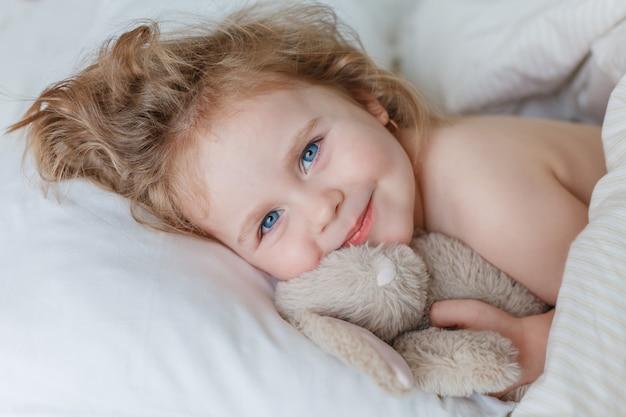 眠っていて、ぬいぐるみのウサギを抱きしめている少女のクローズアップ。リラクゼーション。健康的な睡眠。居心地の良い。