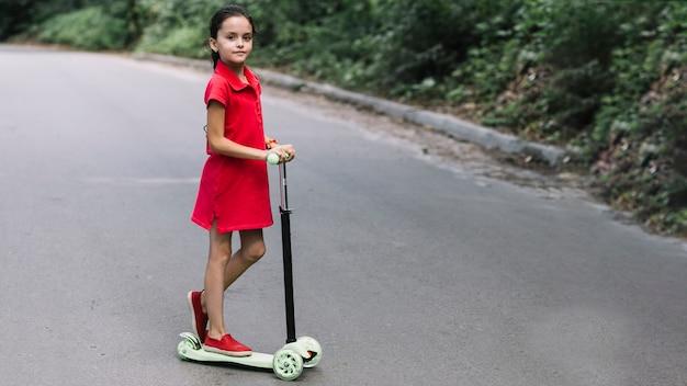 푸시 스쿠터에 서있는 어린 소녀 클로즈업
