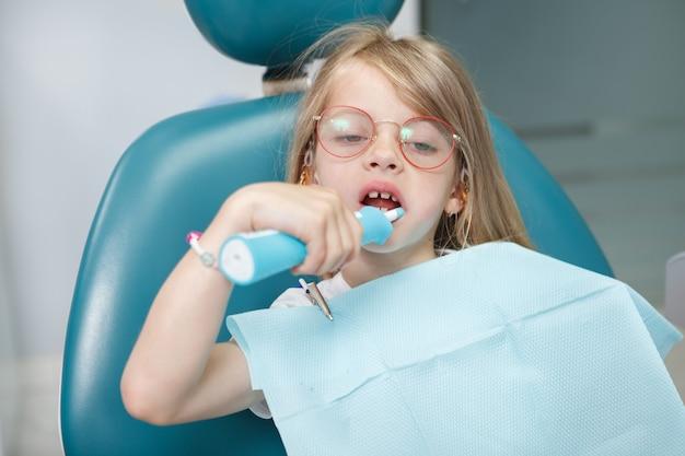 歯科医院で電動歯ブラシで歯を磨く小さな素敵な女の子のクローズアップ