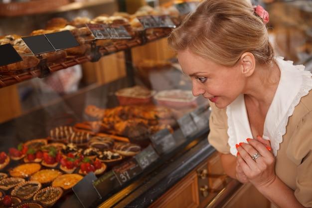 제과점에서 판매할 맛있는 디저트를 보고 있는 사랑스러운 성숙한 여성의 클로즈업