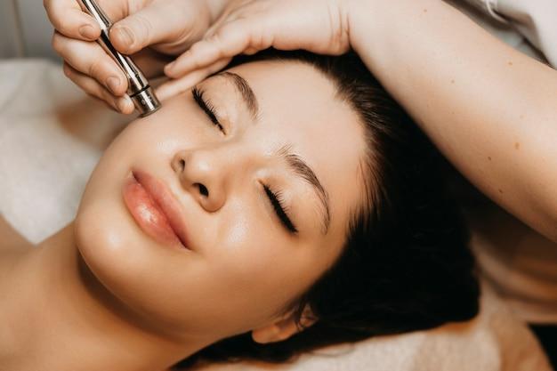 Закройте красивой женщины, имеющей неинвазивную терапию микродермабразией с дерма-ручкой в оздоровительном центре.