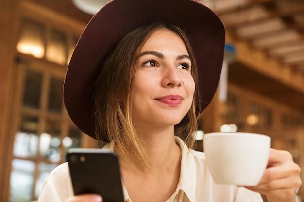 Заделывают прекрасной женщины в шляпе, сидящей за столиком в кафе