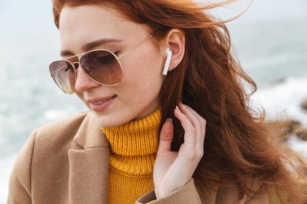 Крупным планом симпатичная молодая рыжая женщина в осеннем пальто гуляет на пляже