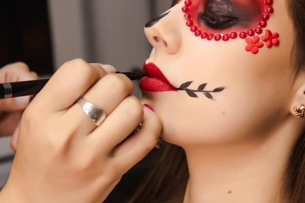 Макро визажиста, рисующего вставные зубы в рот девушки с помощью макияжа dia de los muertos.