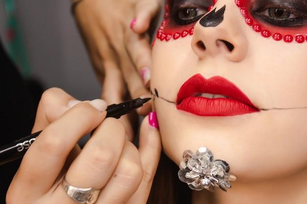 Крупный план визажиста, рисующего рот черепа девушке с макияжем dia de los muertos.