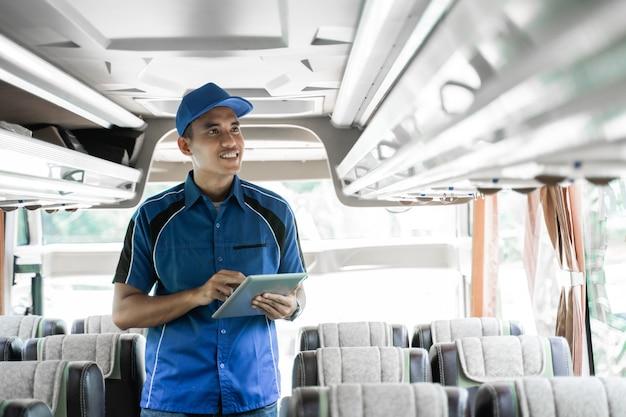 닫기 남성 버스 승무원이 버스 내부의 선반을 확인하면서 디지털 태블릿을 사용합니다.