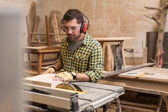 Close-up of a male carpenter cutting a wooden block with circular saw in table