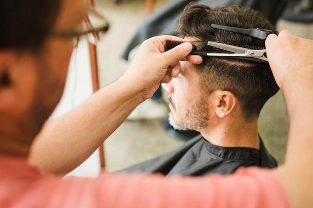 Крупный план клиента мужского пола, получающего стрижку парикмахером