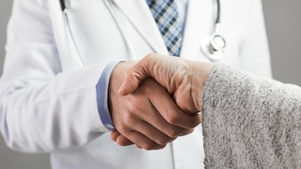 男性医師と患者が手を振ってのクローズアップ