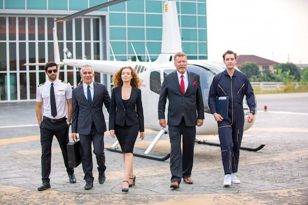 Закройте вверх мужского стекла солнца носки пилота вертолета и бизнесменов или исполнительного директора генерального директора стоя против вертолета на посадочной площадке воздушных судн в авиапорте на яркий солнечный день.