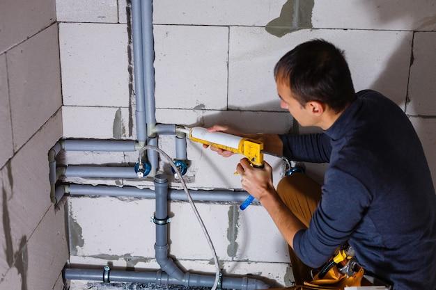 Крупным планом мужчина-сантехник ремонтирует трубы в туалете