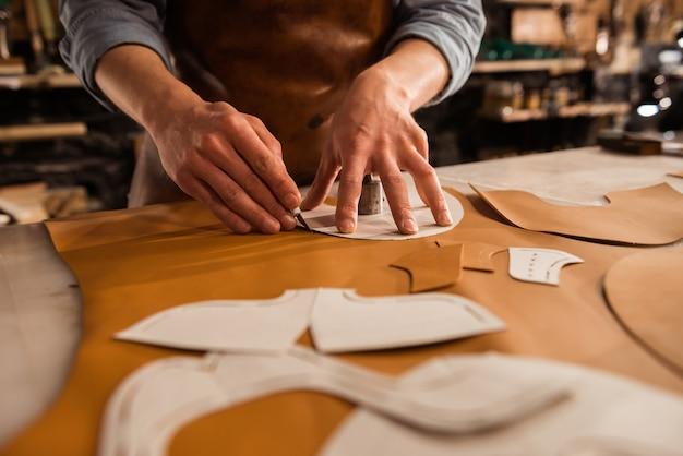 Крупным планом мужской сапожник резки кожи текстиля