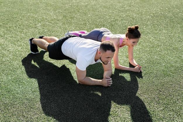 Крупный план мужчины и женщины, делающих планку на траве на спортивном стадионе на закате
